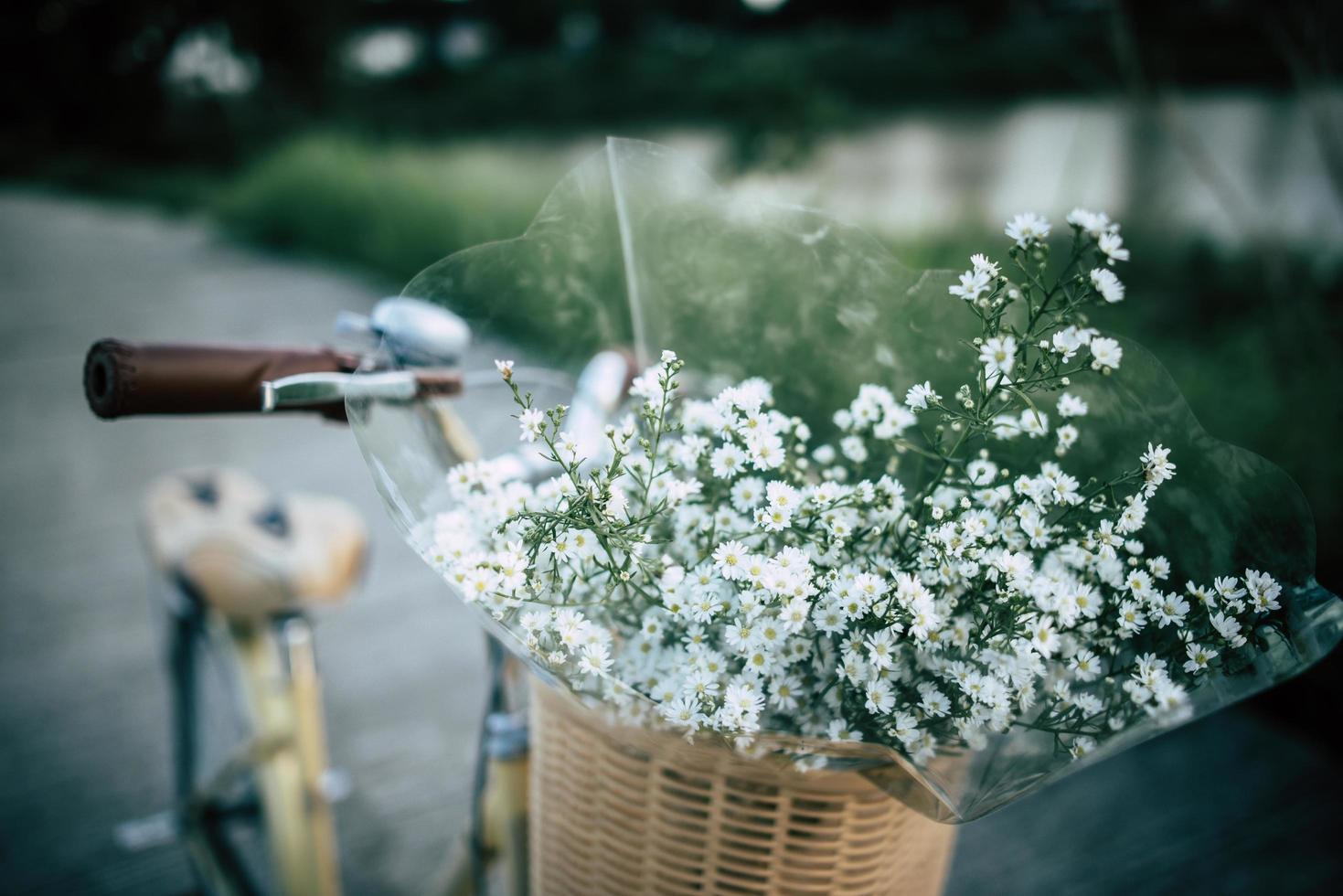 Bicicleta vintage con una canasta llena de flores silvestres foto