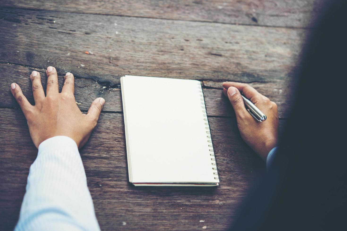 Man writing on blank notebook on wooden table photo