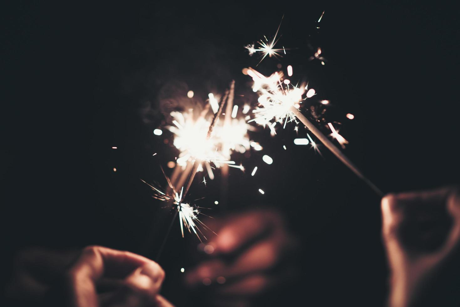Group of people holding sparklers at night photo