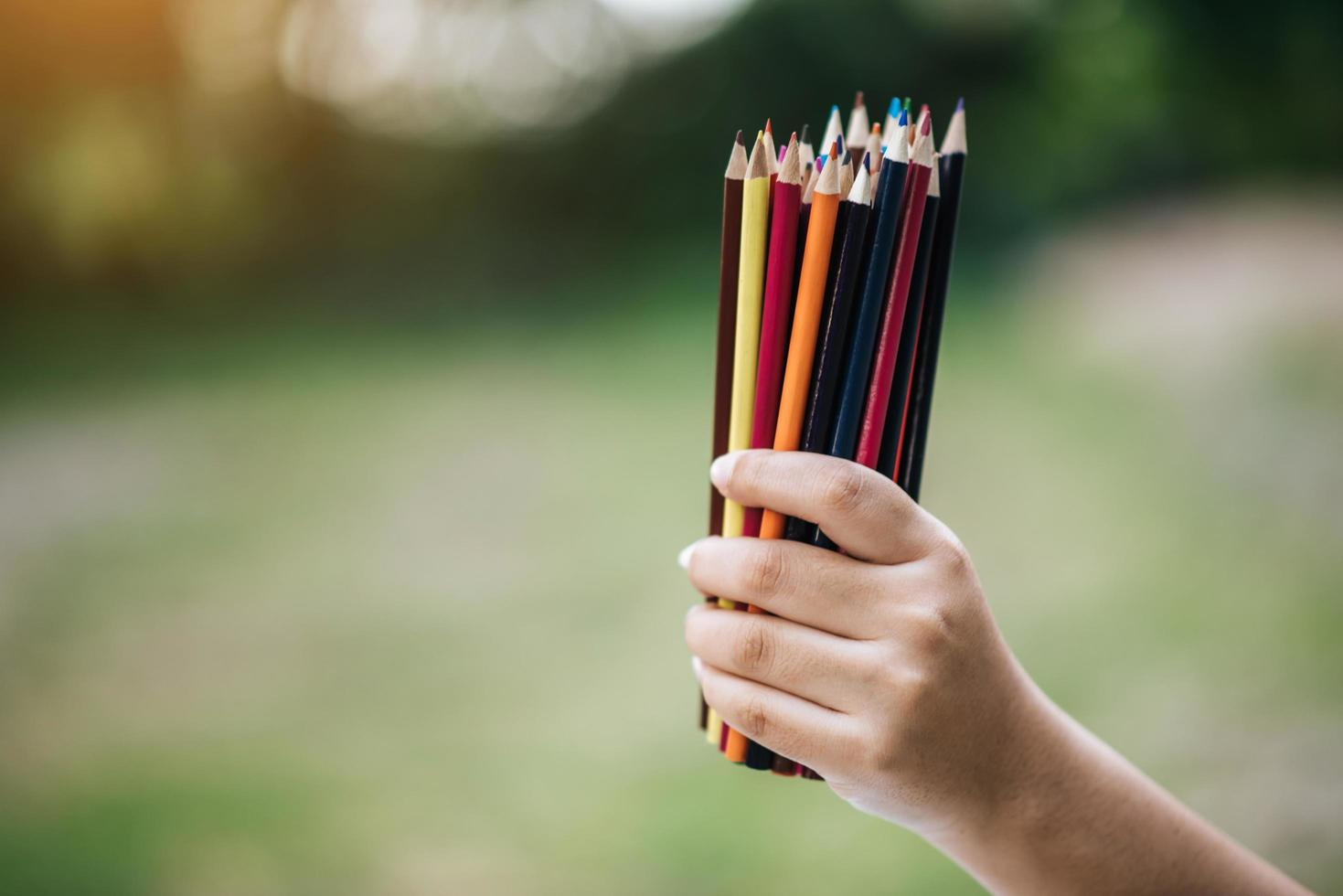 Colorful pencils in hand on green background photo