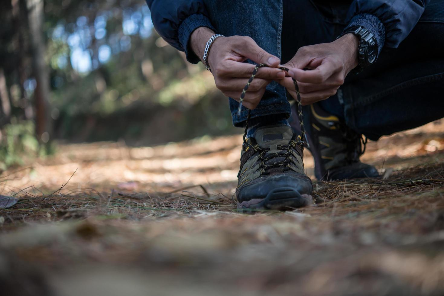 Young hiker man ties his shoe laces while backpacking in the forest photo