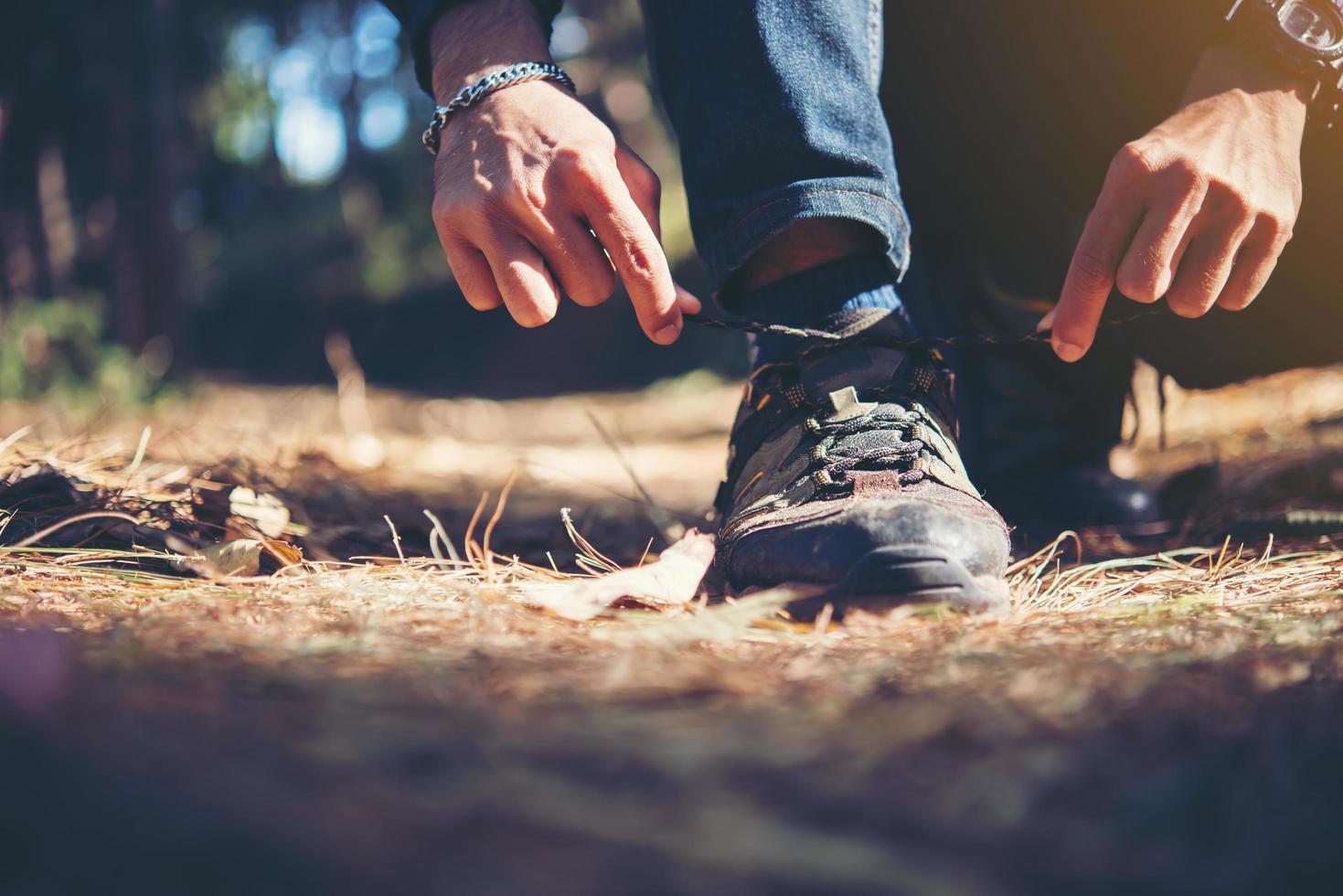 Hombre joven excursionista ata los cordones de sus zapatos mientras viaja con mochila en el bosque foto