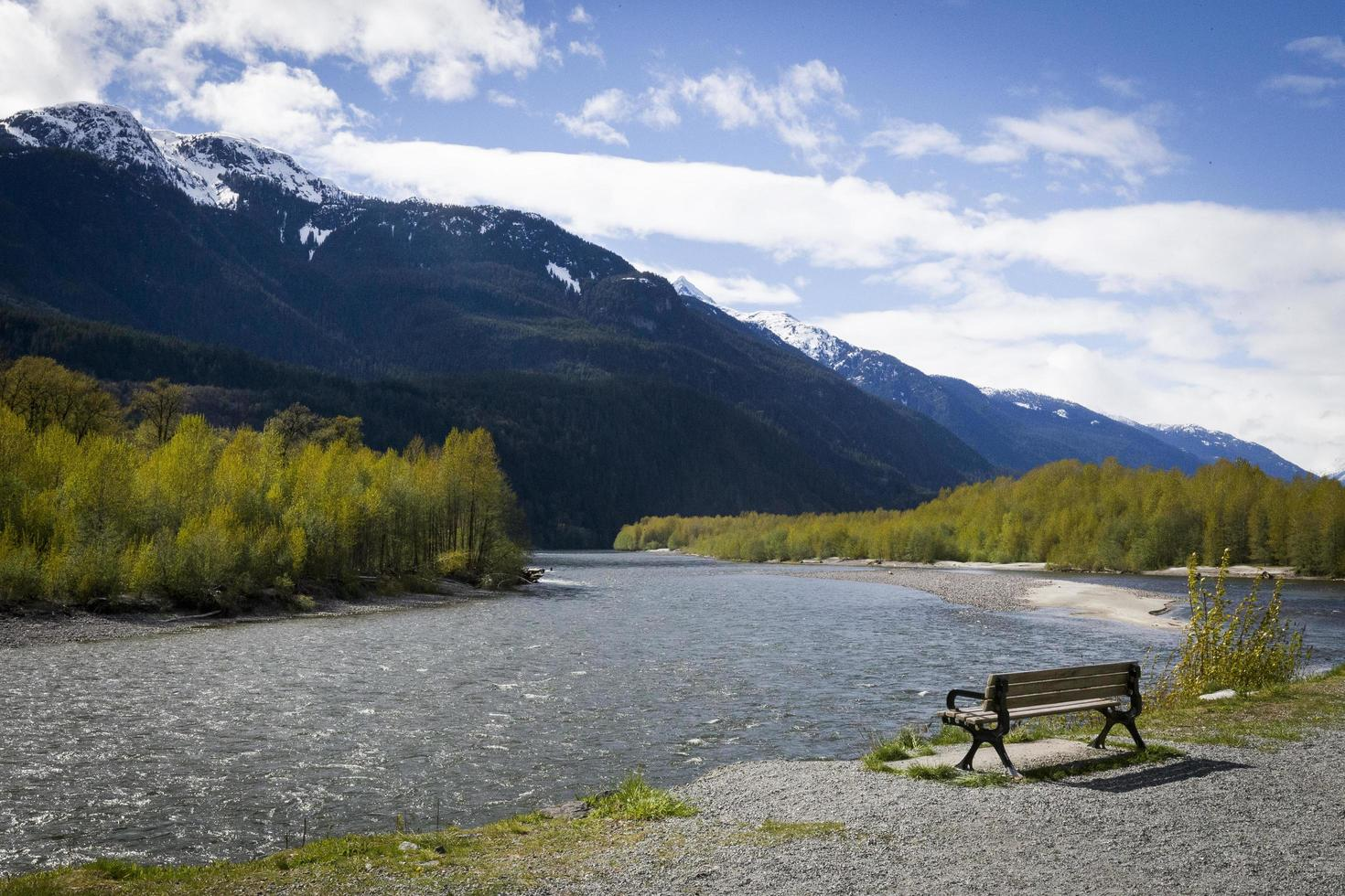 Bench by a river and mountain photo