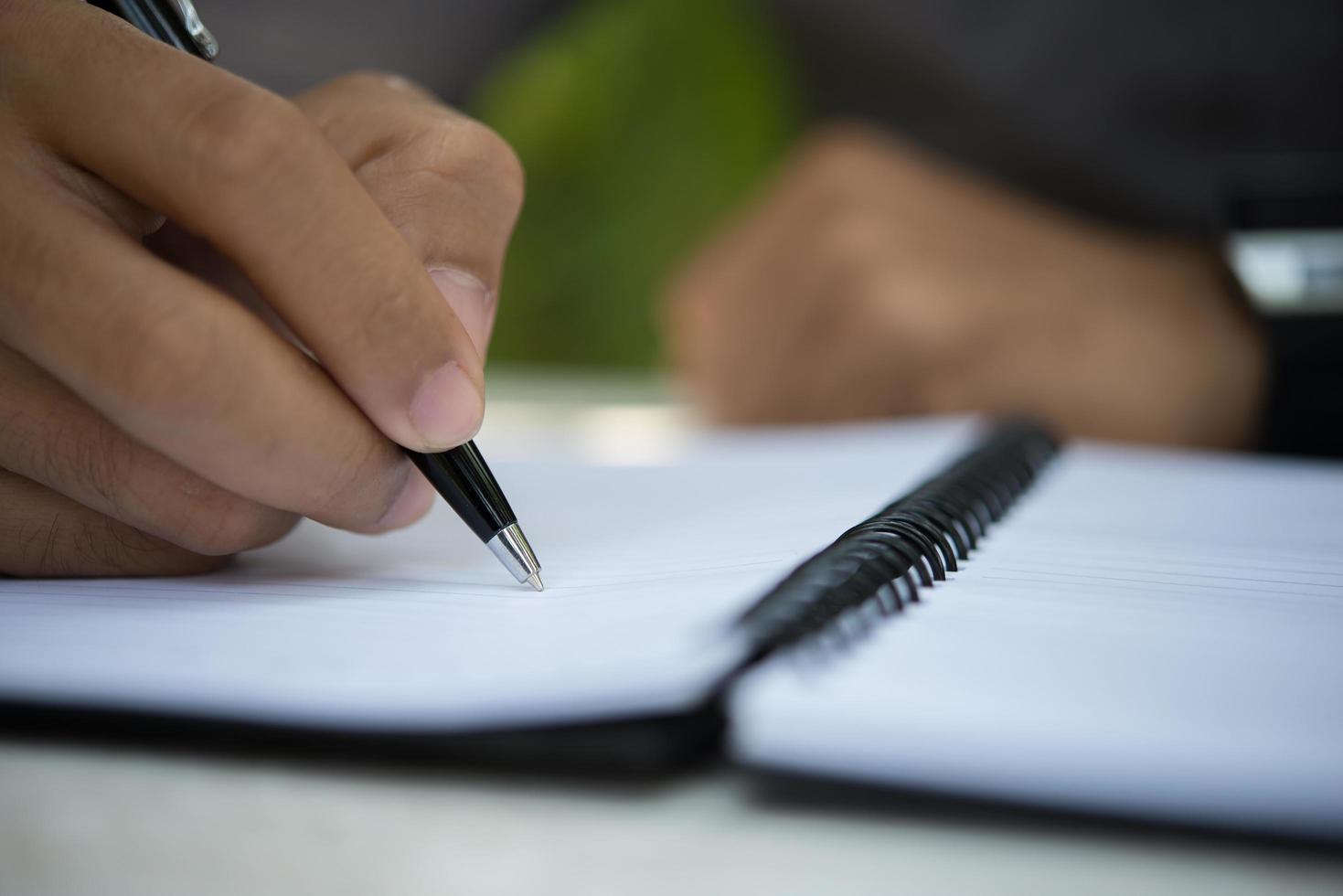 Hombre escribiendo en el bloc de notas mientras está sentado relajándose en el jardín de su casa foto
