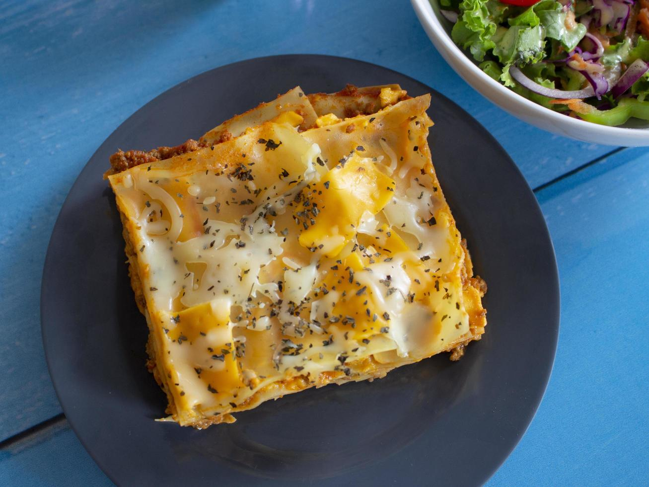 Homemade lasagna with a side salad photo