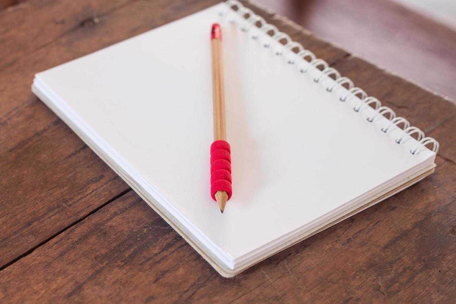 Notebook and pencil on a wood table photo