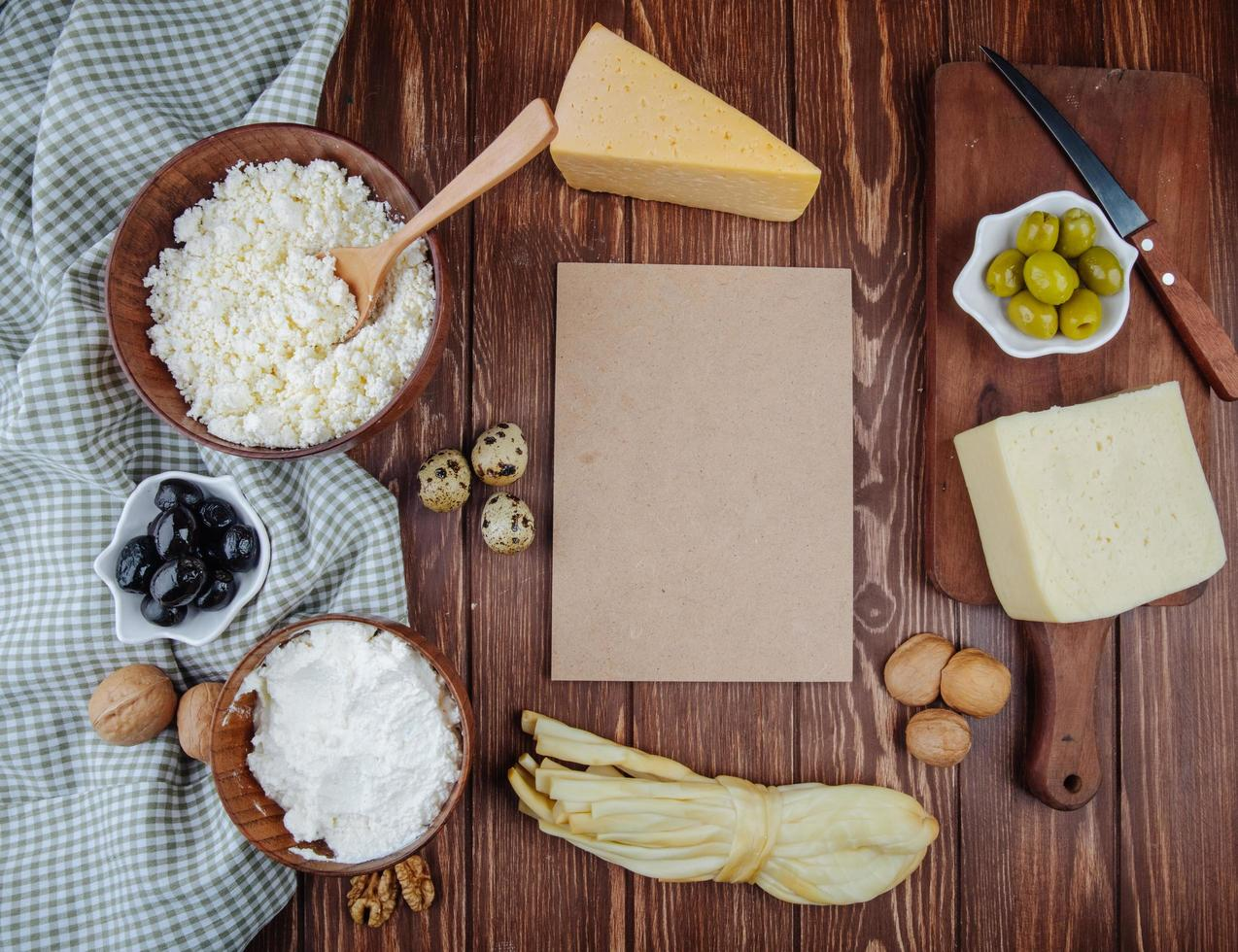 Vista superior de papel marrón con queso y otros aperitivos. foto