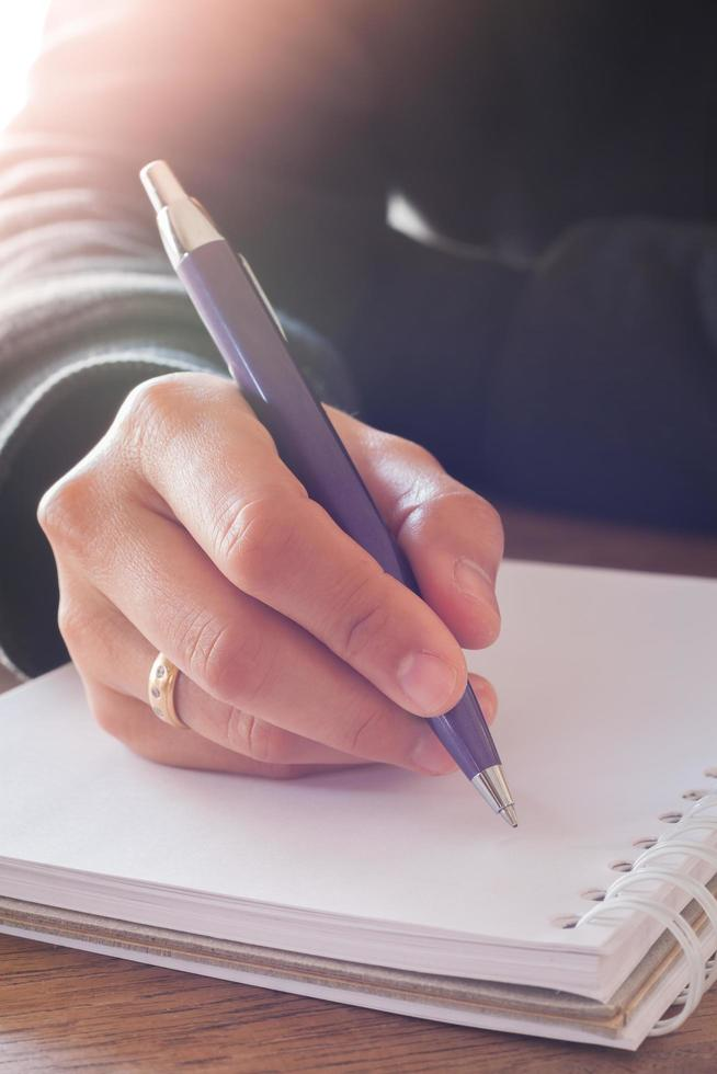 Person writing in a notebook on a table photo
