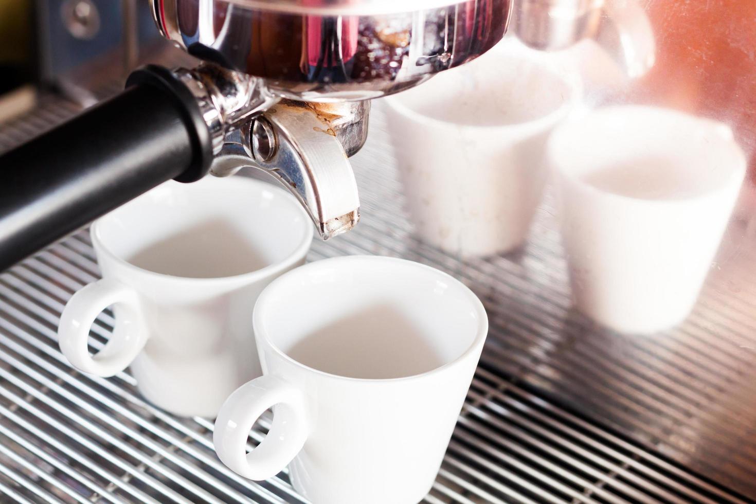 tazas de espresso debajo de una máquina de espresso foto