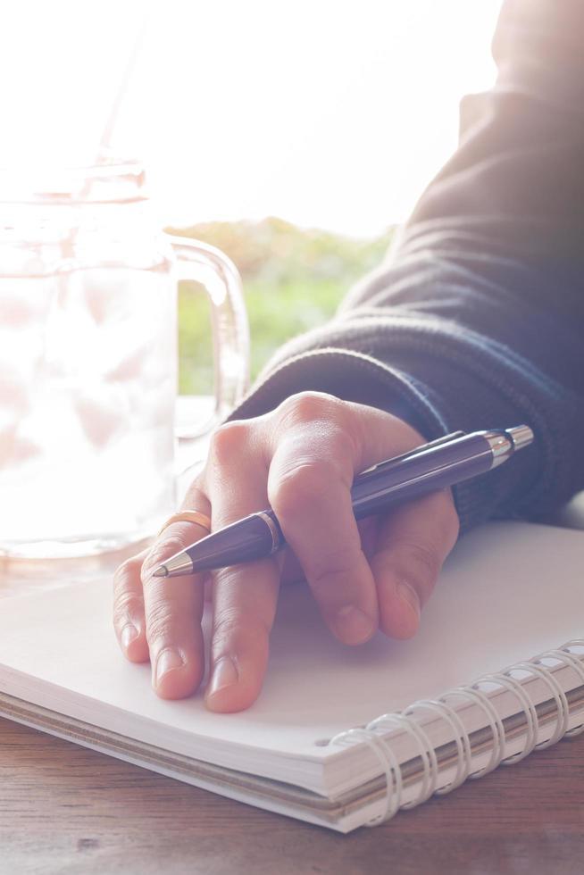 mano sosteniendo un bolígrafo en un cuaderno foto