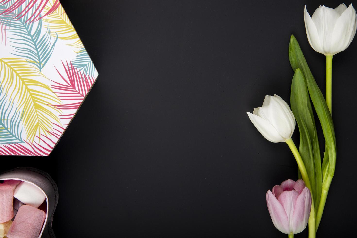 tulipanes y tela sobre un fondo negro con espacio de copia foto