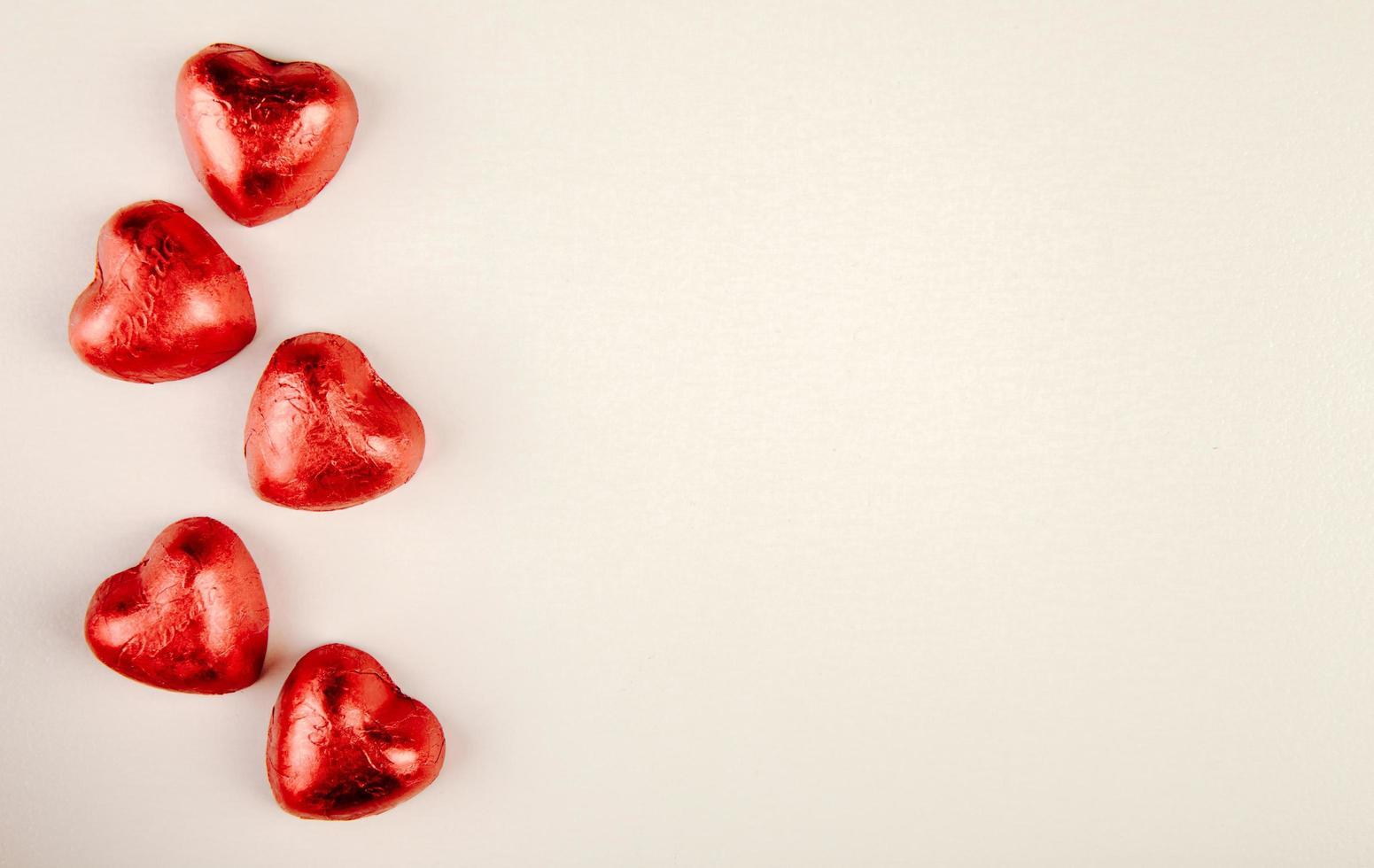 Caramelos en forma de corazón sobre un fondo blanco con espacio de copia foto