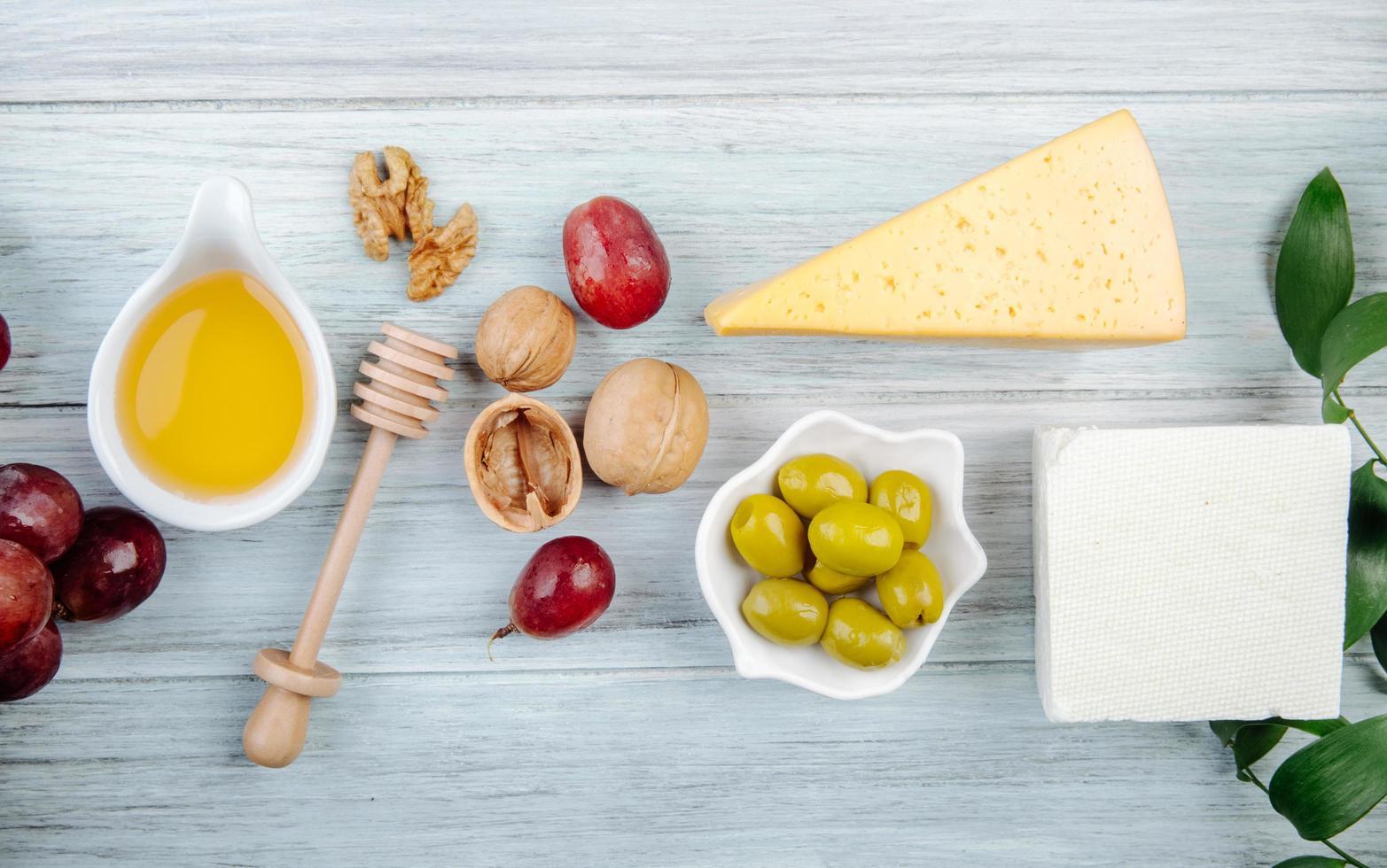Vista superior de queso con miel, uvas, nueces y aceitunas. foto