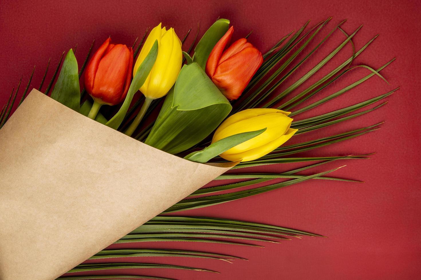 Vista superior de un ramo de tulipanes rojos y amarillos en papel kraft foto