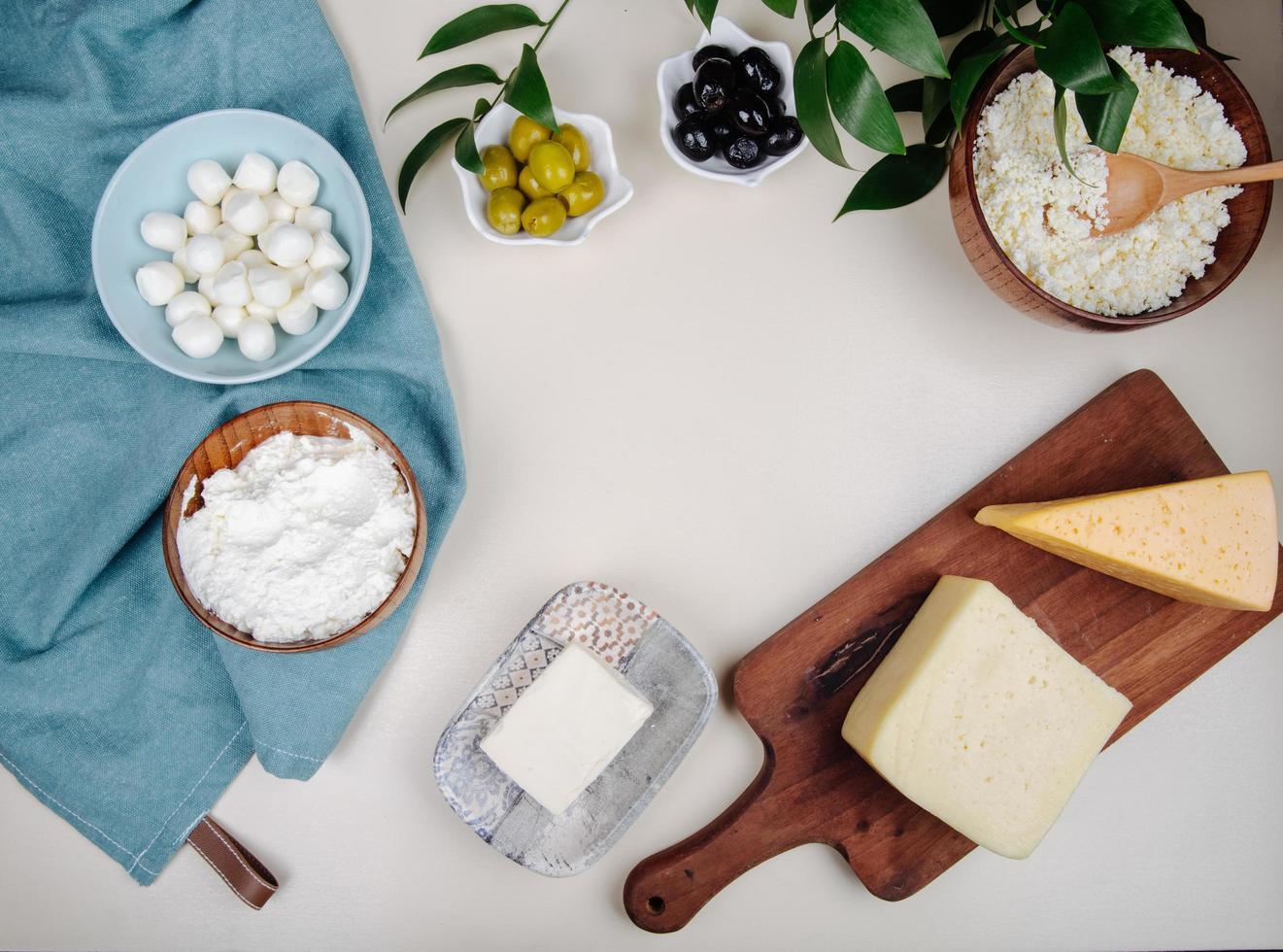 Vista superior del queso sobre una tabla de cortar de madera con aceitunas y sal foto