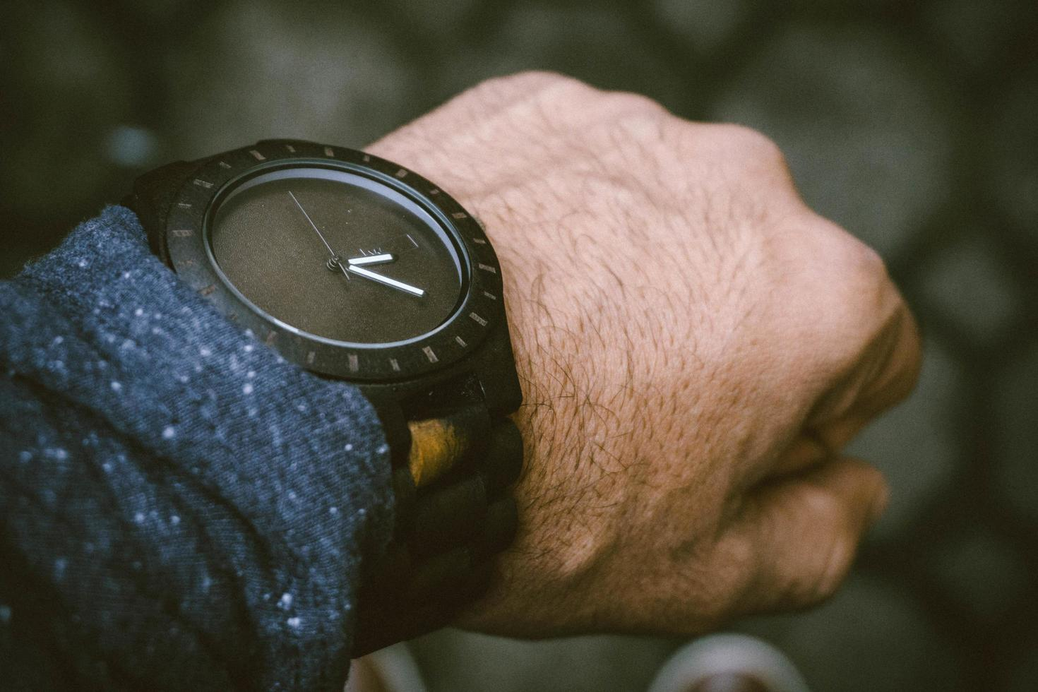 reloj analógico negro en la muñeca humana izquierda foto