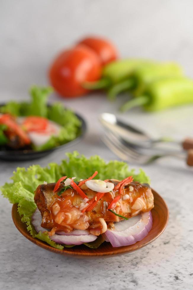 Ensalada de sardina picante en un cuenco de madera foto