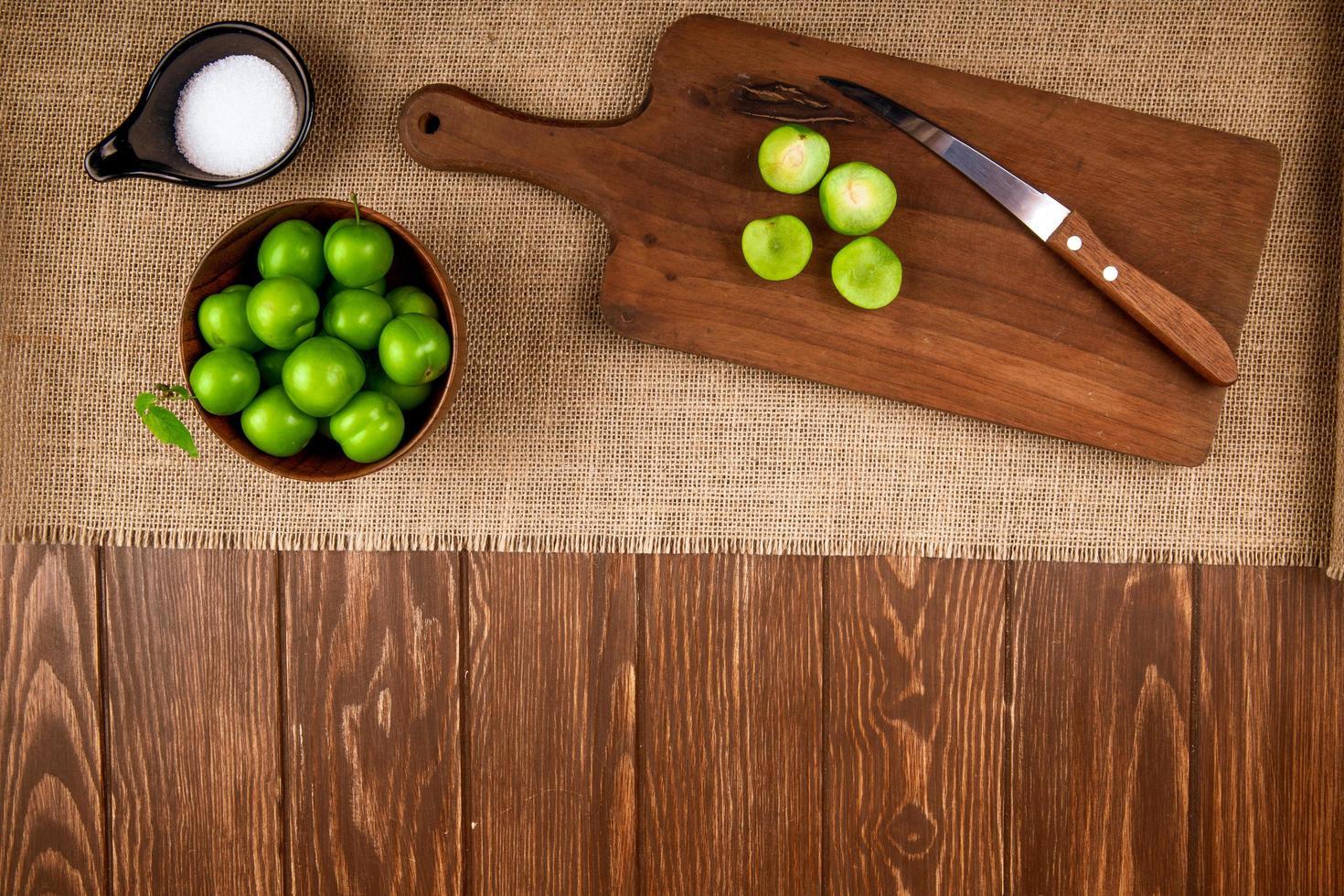 Vista superior de ciruelas verdes ácidas en un recipiente y sobre una tabla de cortar de madera foto