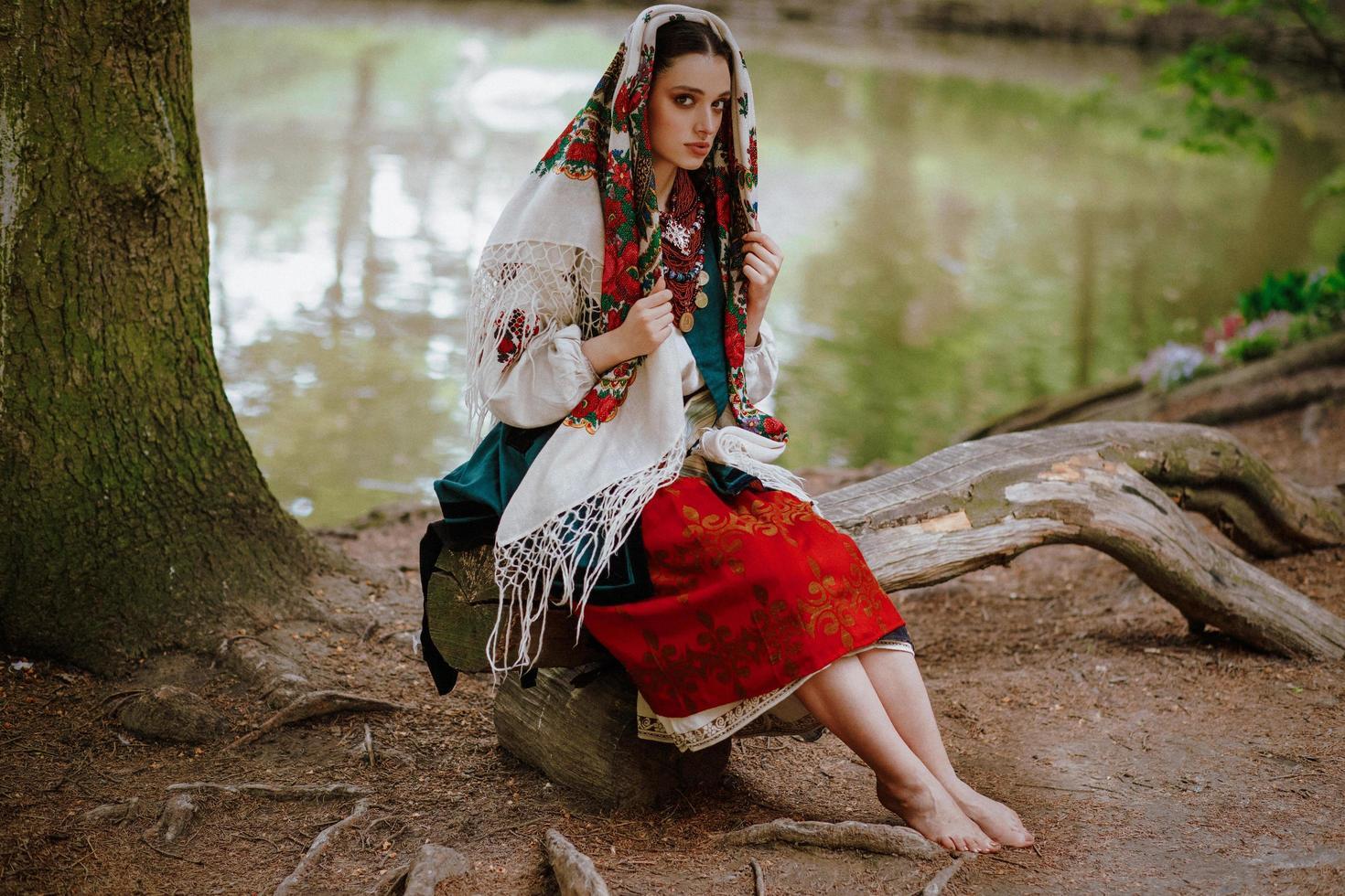niña ucraniana sentada junto al lago foto