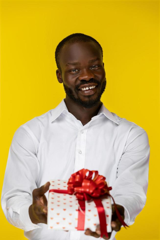 Portrait of cute man giving a gift photo