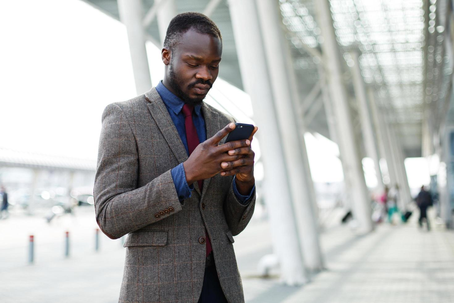 Businessman typing on his phone photo