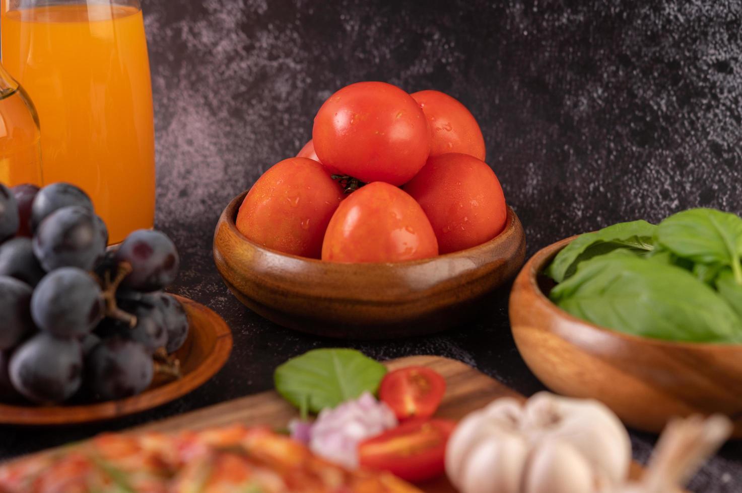 tomates frescos, uvas y jugo de naranja en un vaso foto