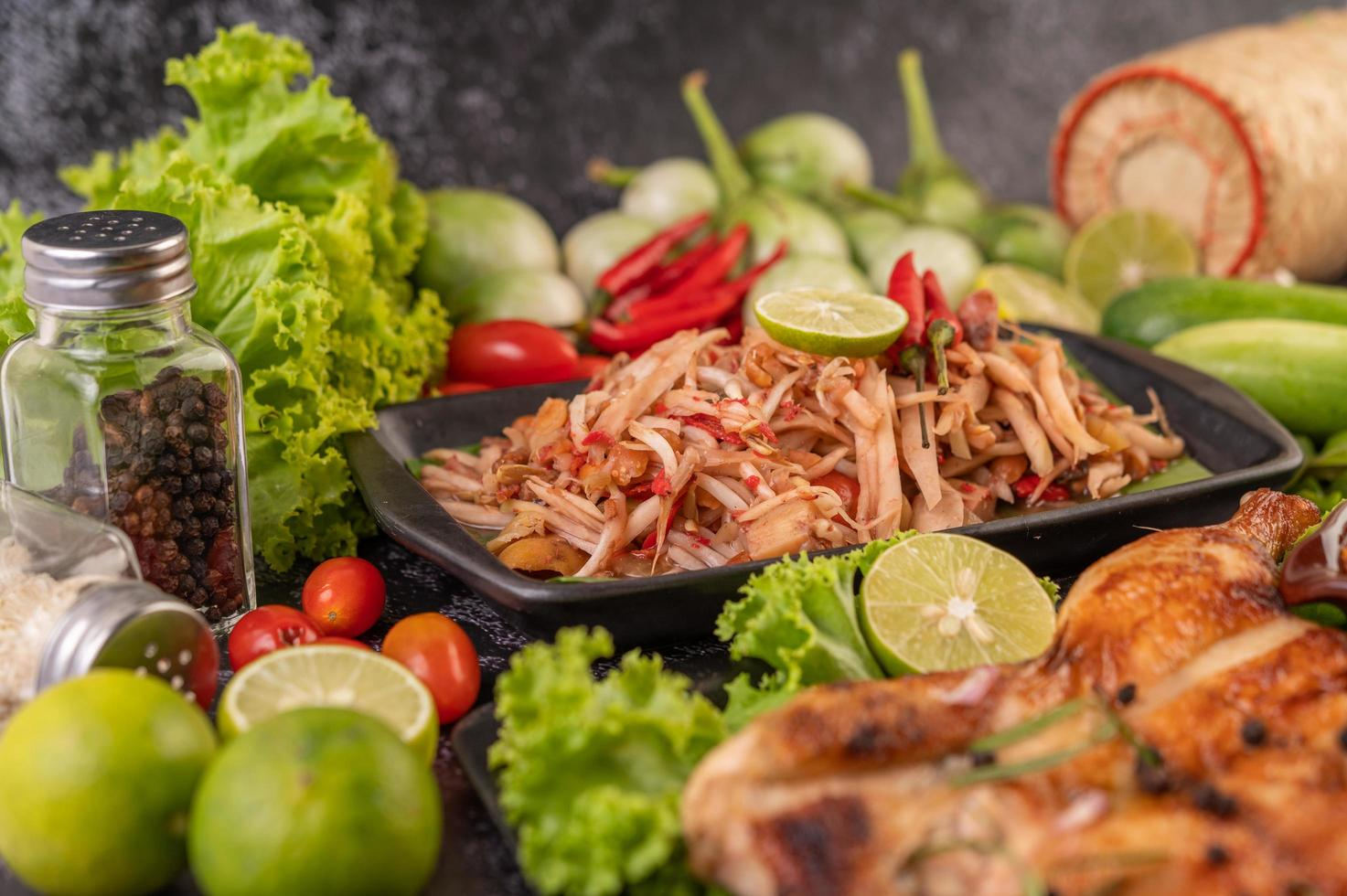 Thai papaya salad surrounded by vegetables and chicken photo