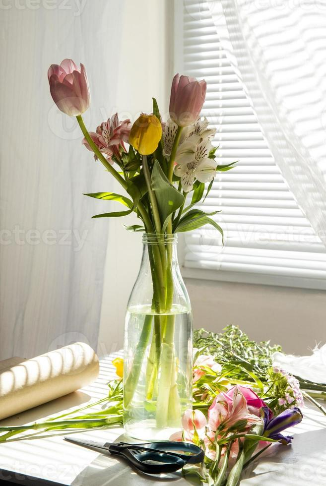 Bouquet of pink and yellow tulips on a table photo