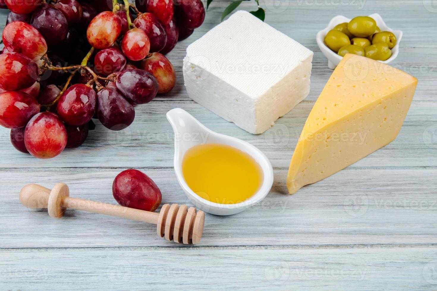 primer plano de miel, queso y otros aperitivos foto