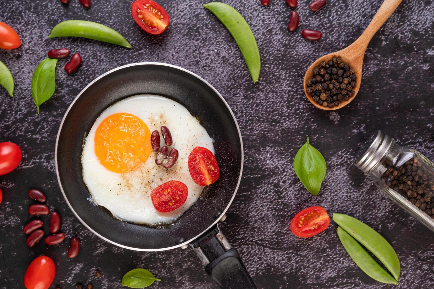 Fried egg in a frying pan with tomato photo