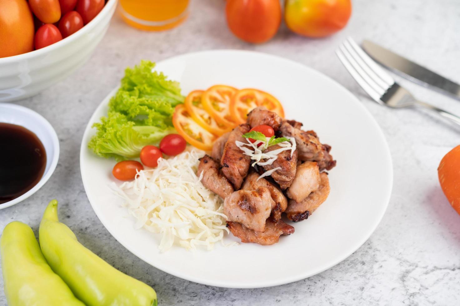 Chuleta de cerdo a la plancha con tomate y ensalada foto