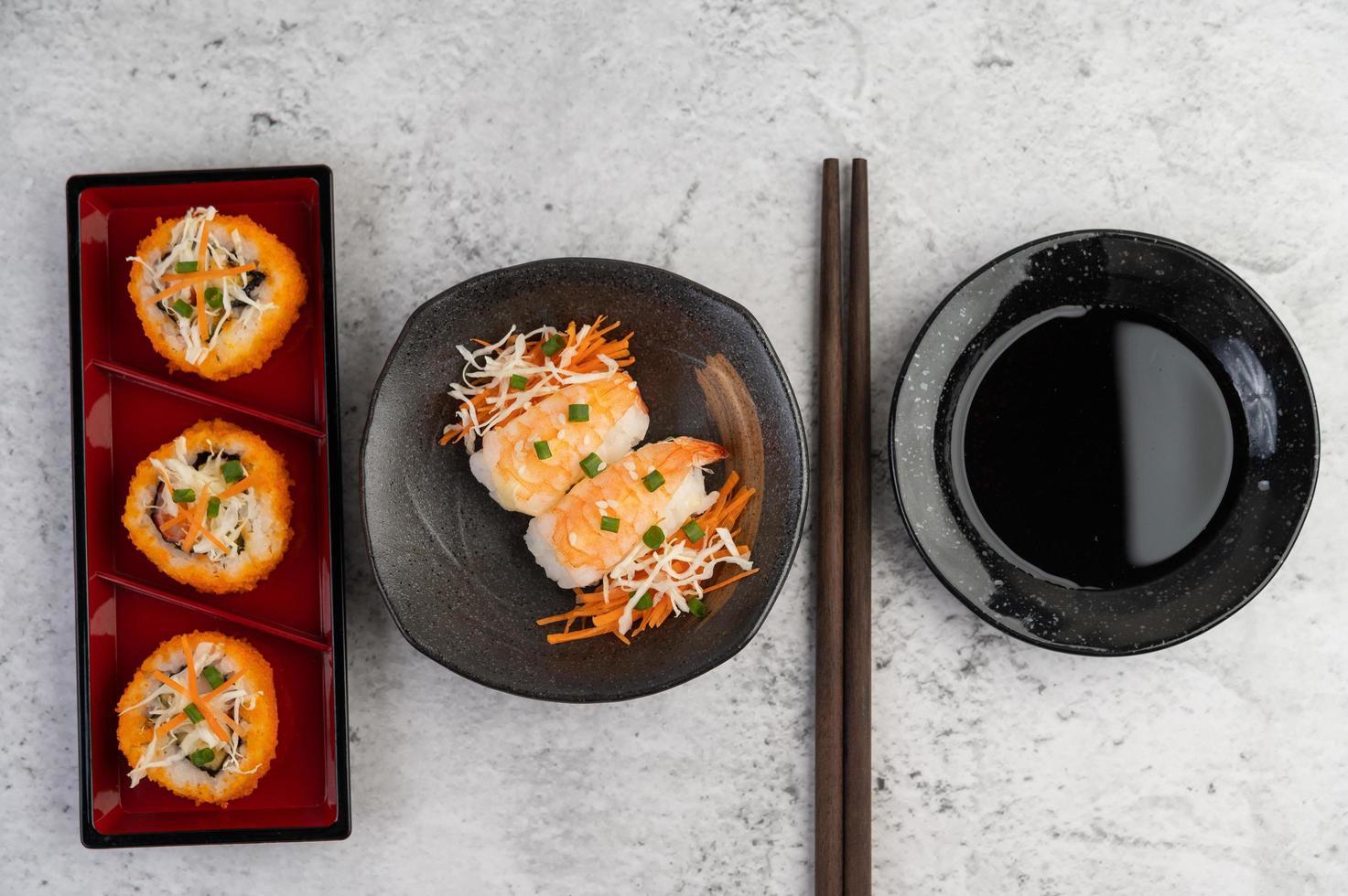 sushi plateado con salsa y palillos foto