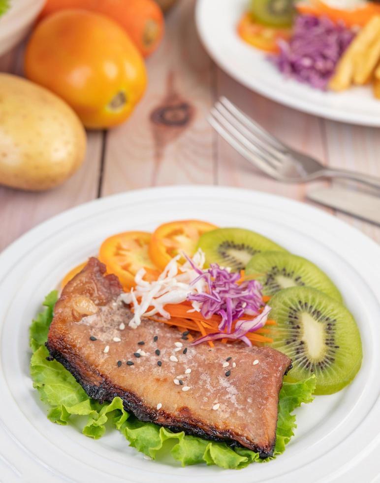 Filete de pescado con patatas fritas, frutas y verduras. foto