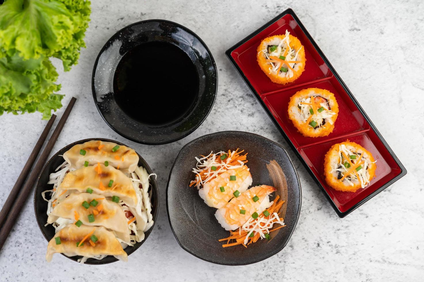 Plated sushi with sauce and chopsticks photo