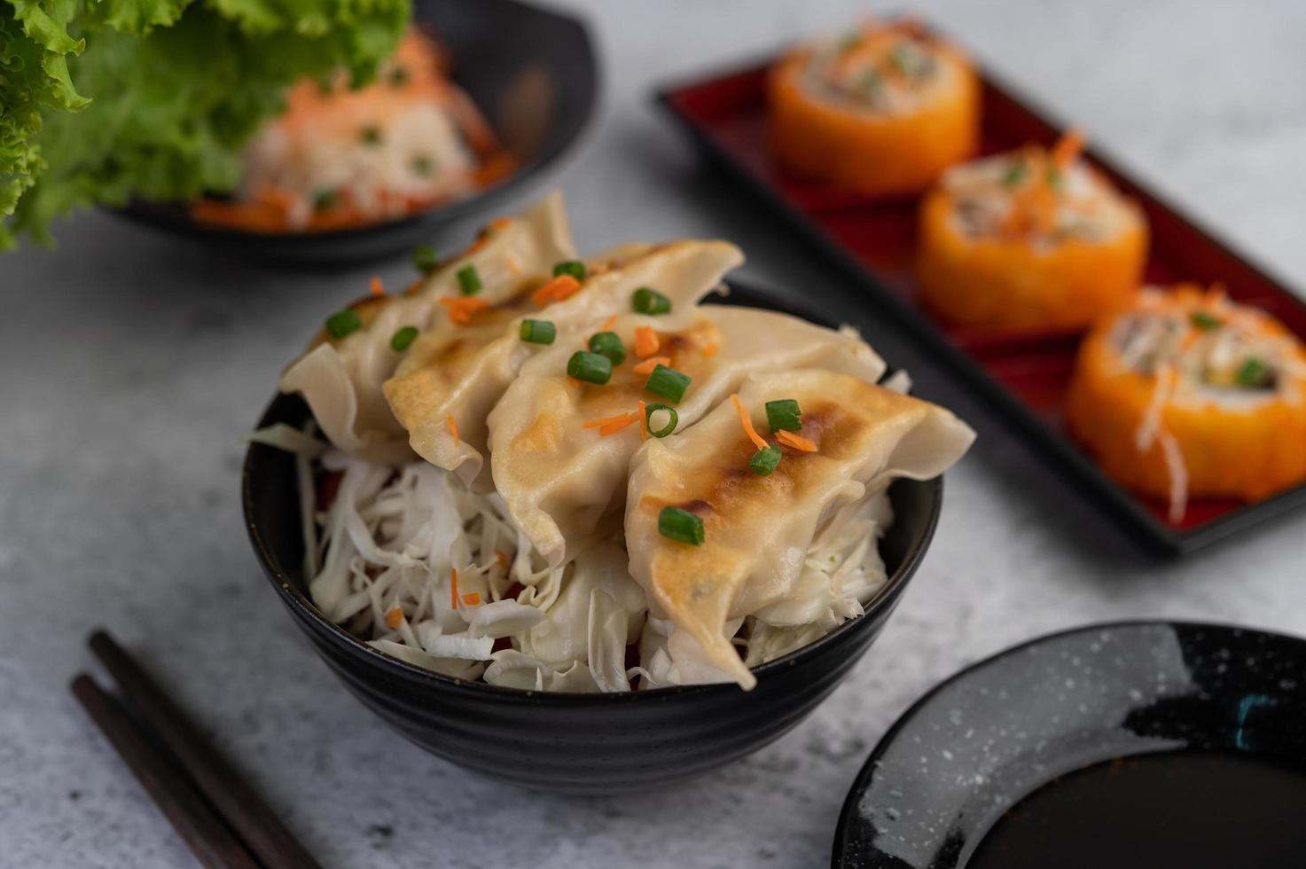 Gyoza in a black cup with sauce photo