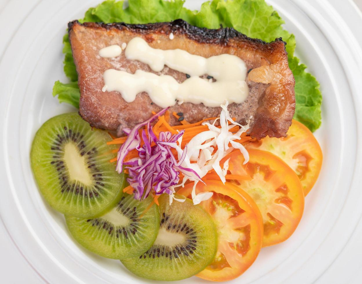 Fish steak with french fries, fruit and vegetables photo