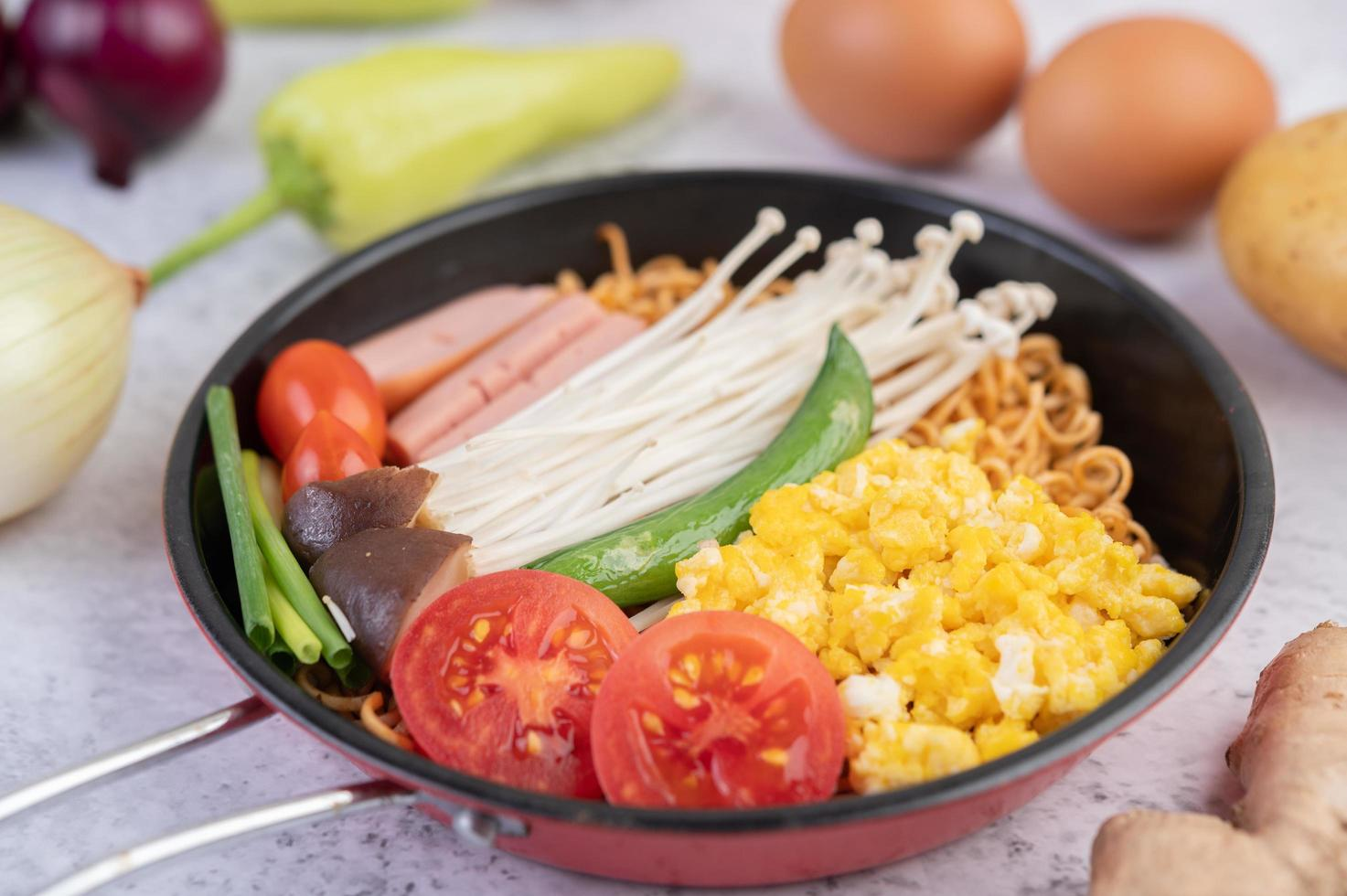 Stir-fried noodles with corn, golden needle mushroom, tomato, sausage and edamame photo