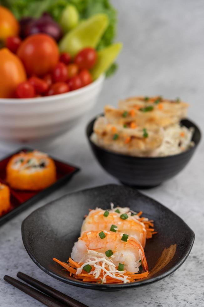 sushi plateado con palillos y salsa para mojar foto
