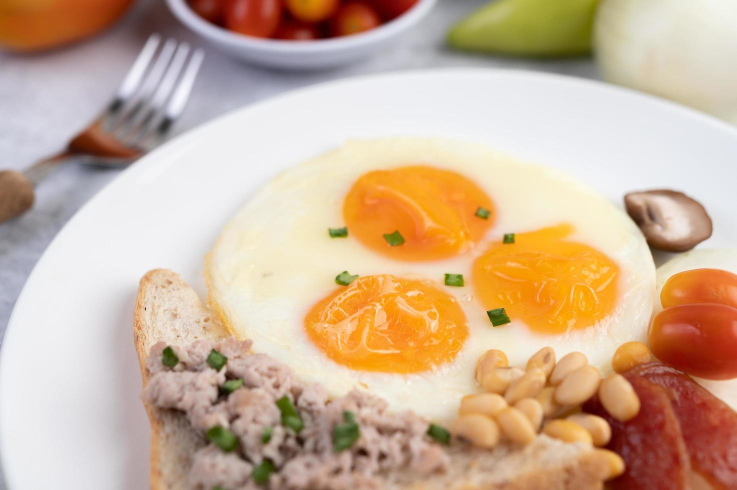 Fried eggs, sausage, minced pork, bread and red beans photo