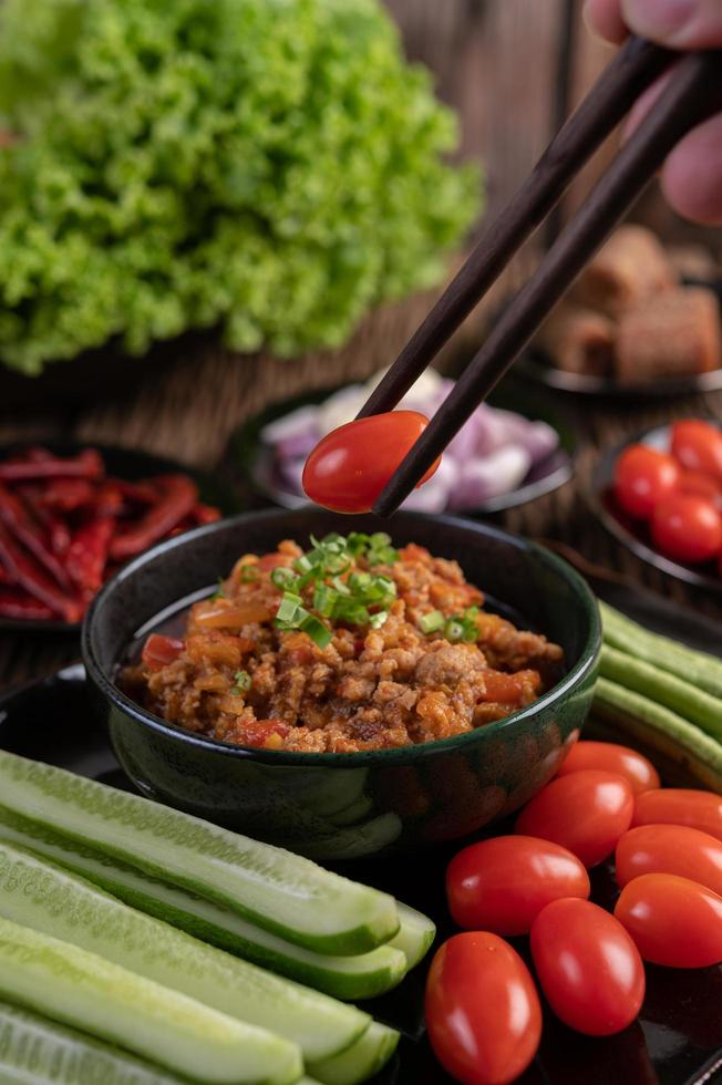 Sweet pork with cucumbers, long beans, tomatoes, and side dishes photo