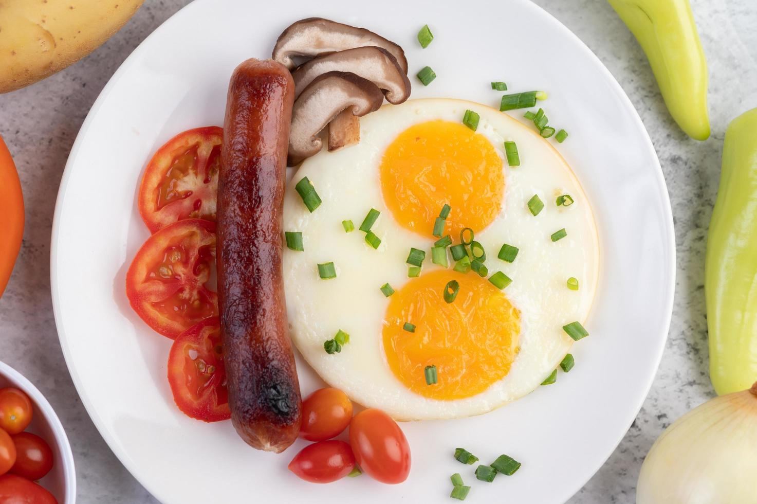 Breakfast plate with fried eggs, tomatoes, Chinese sausage and mushrooms photo