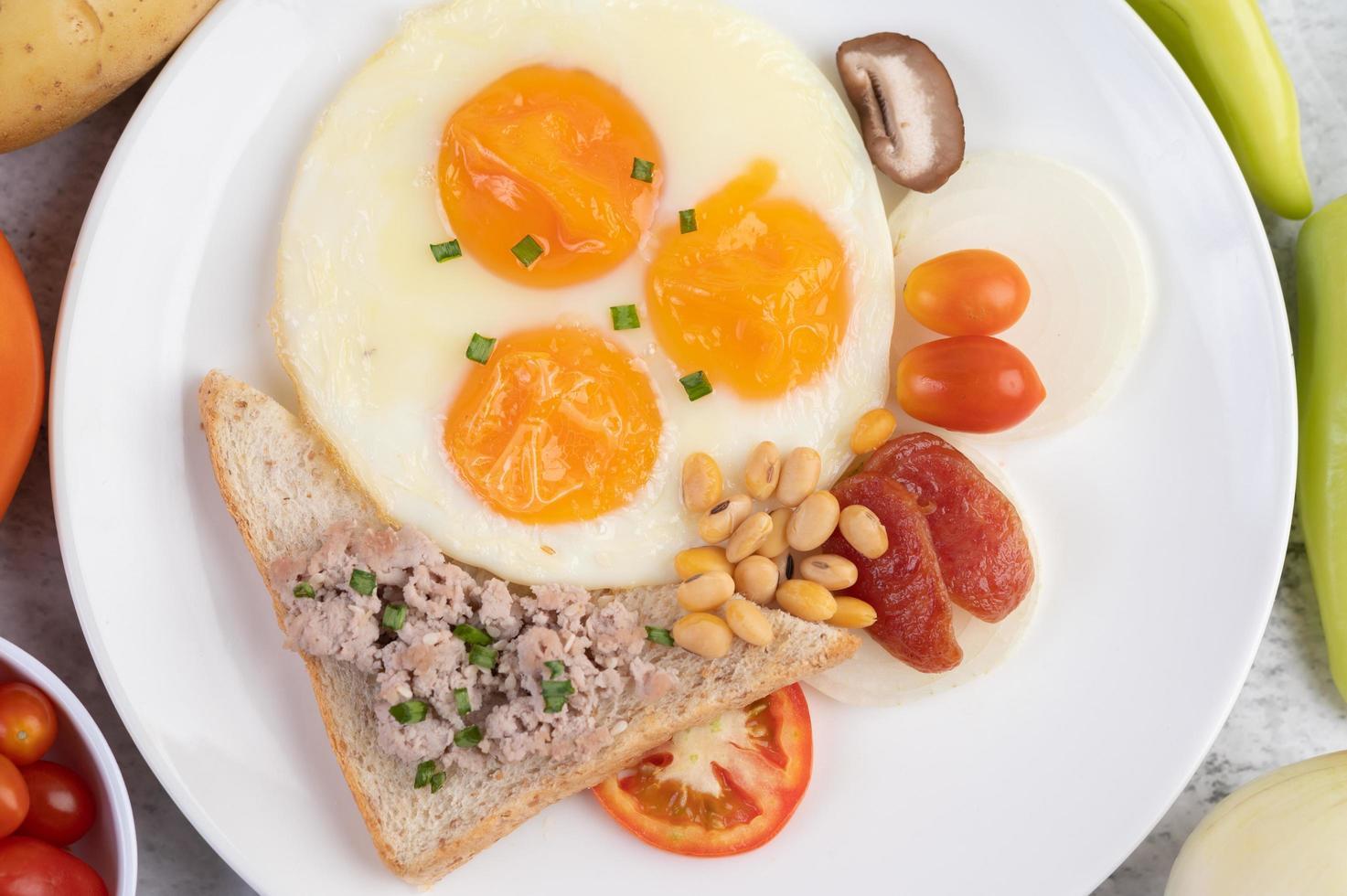 huevos fritos, salchicha, carne de cerdo picada, pan y frijoles rojos foto