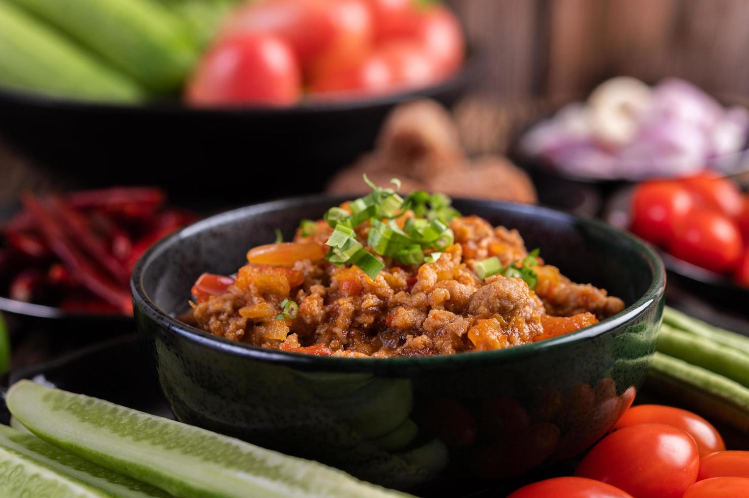 Sweet pork with cucumbers, long beans, tomatoes and side dishes photo