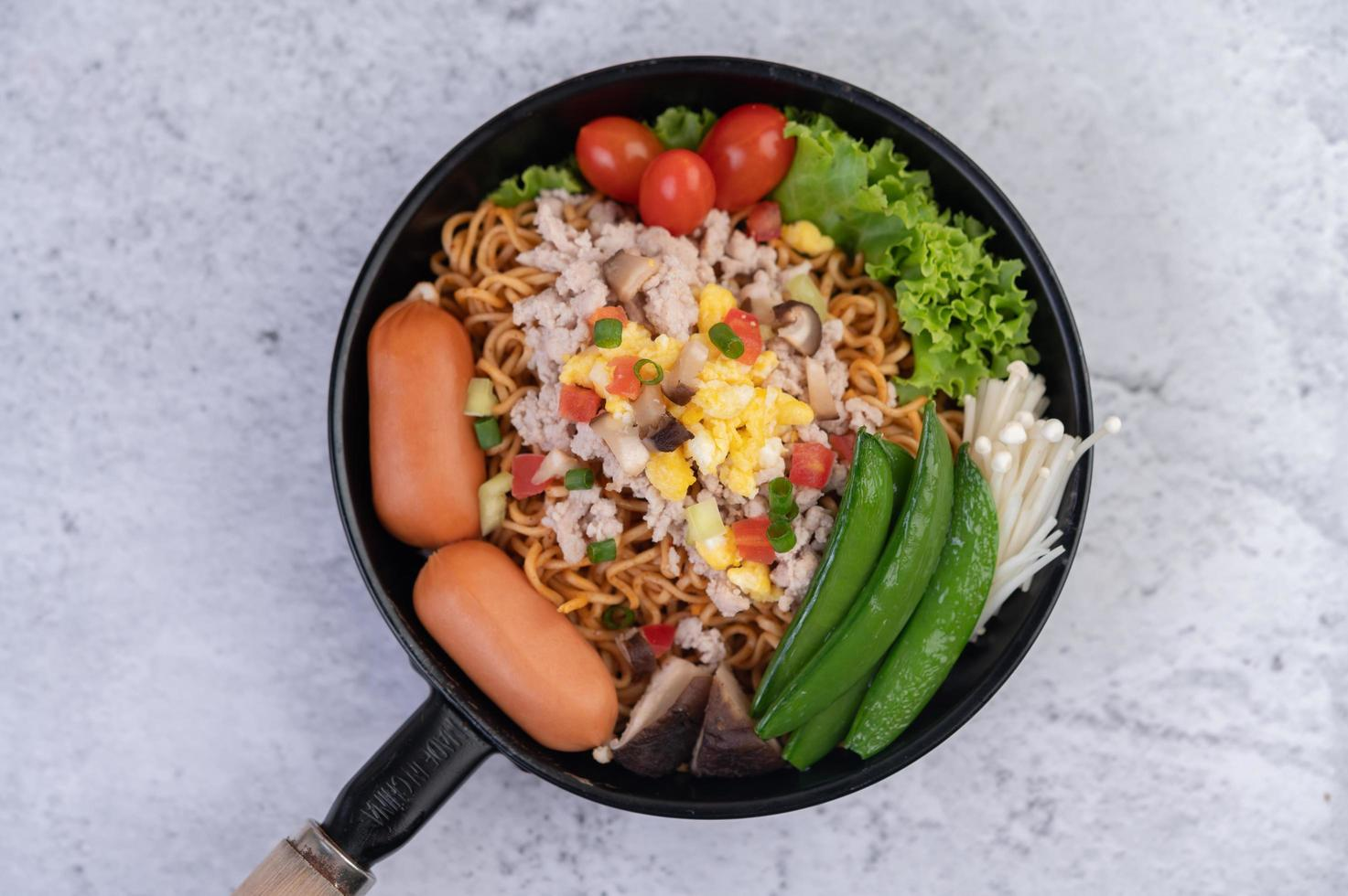 Stir-fried noodles with minced pork, edamame, tomatoes and mushrooms photo