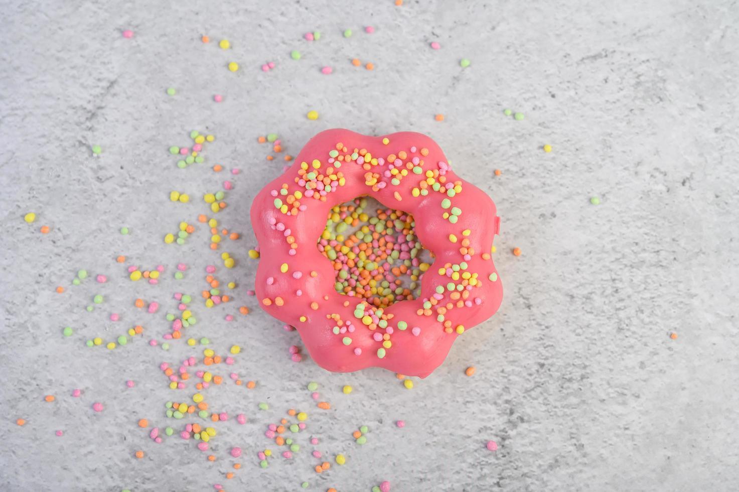 rosquilla de fresa decorada con glaseado y chispas foto
