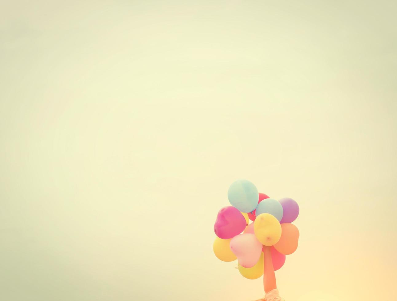 Hands holding colorful balloons in the sunshine of summer photo