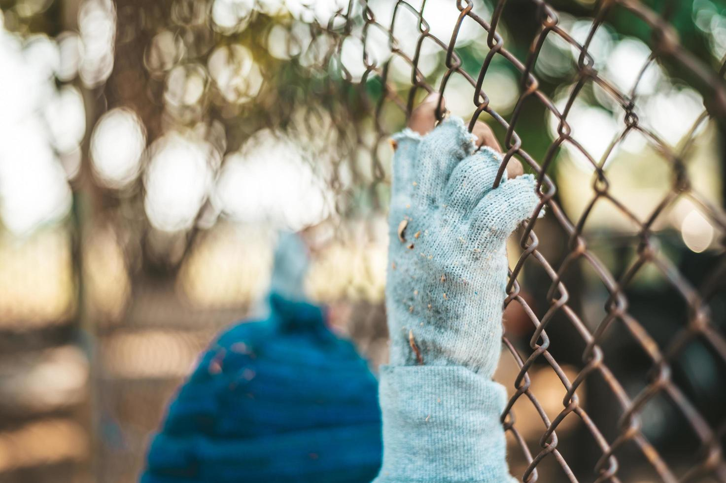 Hands grabbing a metal fence photo