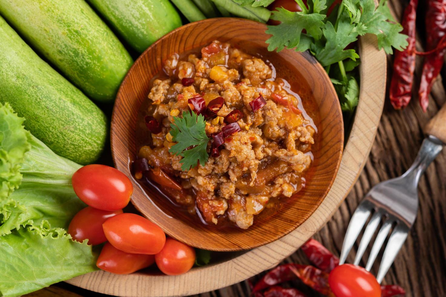 Sweet pork in a wooden bowl with ingredients photo