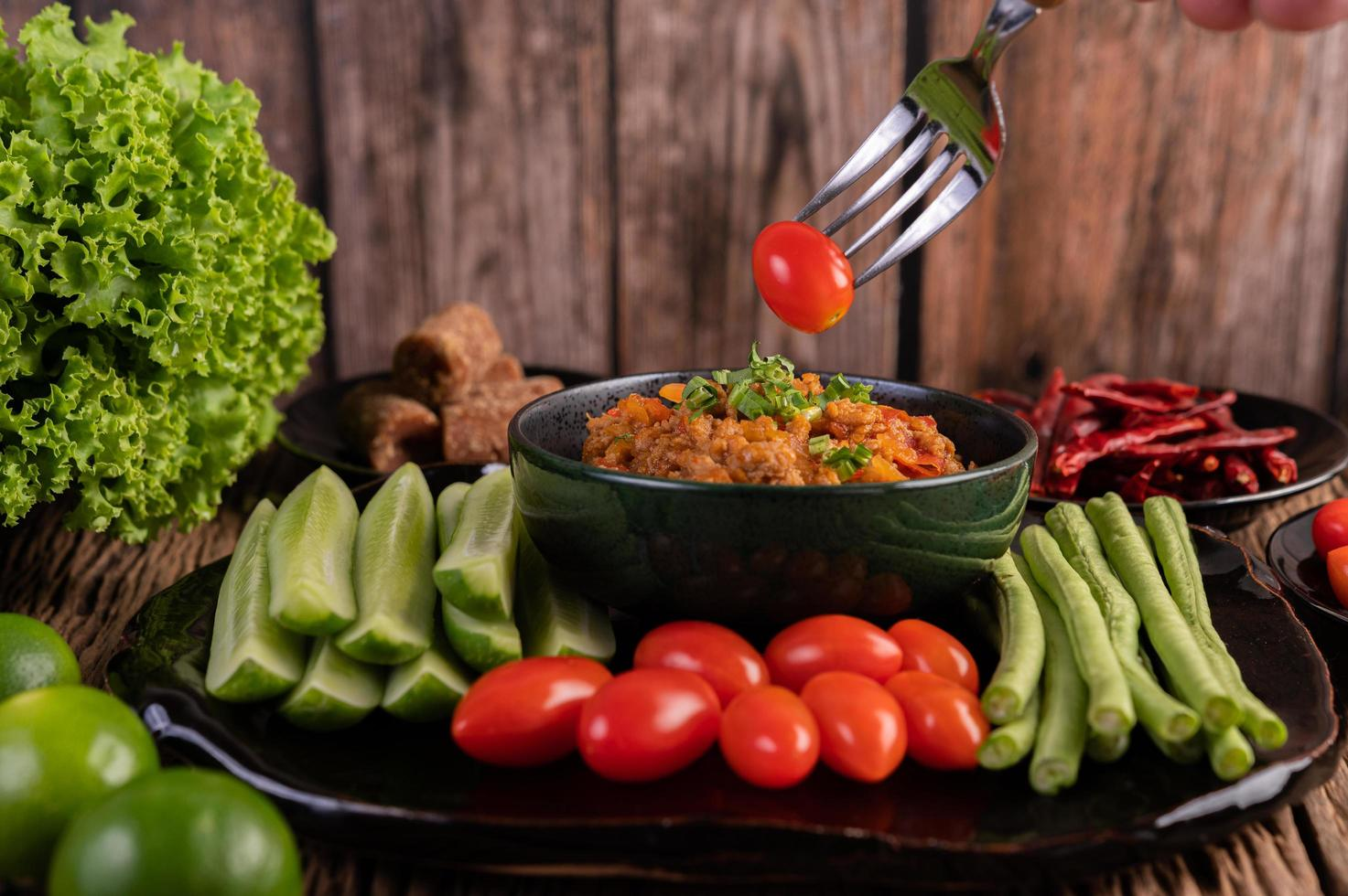 Pork with cucumbers, long beans, tomatoes and side dishes photo