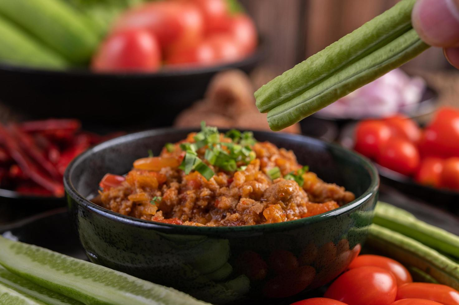 Sweet pork bowl with cucumbers, long beans and tomatoes photo